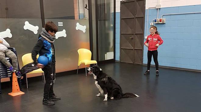 Due ragazzi dei centri educativi giocano con un cane